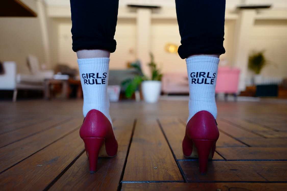 Person Wearing Pair of White Girls Rule Text-printed Socks