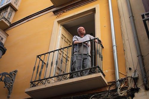 Kostenloses Stock Foto zu balkon, gelb, mann