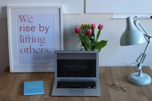 Comfortable desk with opened netbook book and cozy lamp placed near framed image with inscription we raise by lifting others