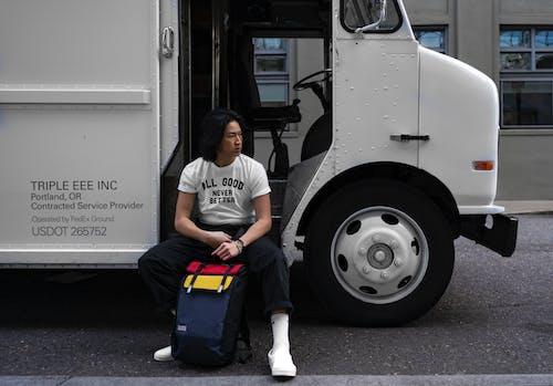 Бесплатное стоковое фото с автомобиль, белые туфли, грузовик, держа сумку