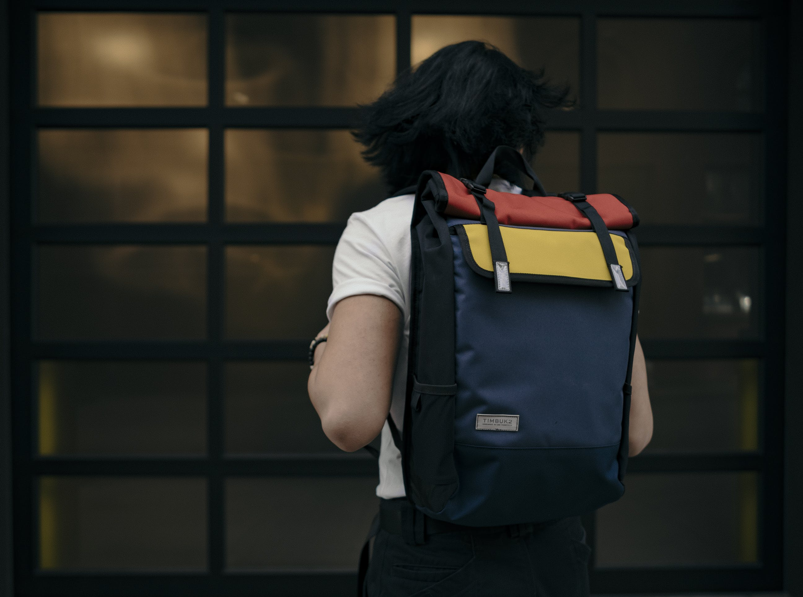 Man Standing While Wearing Black, Red, and Yellow Backpack