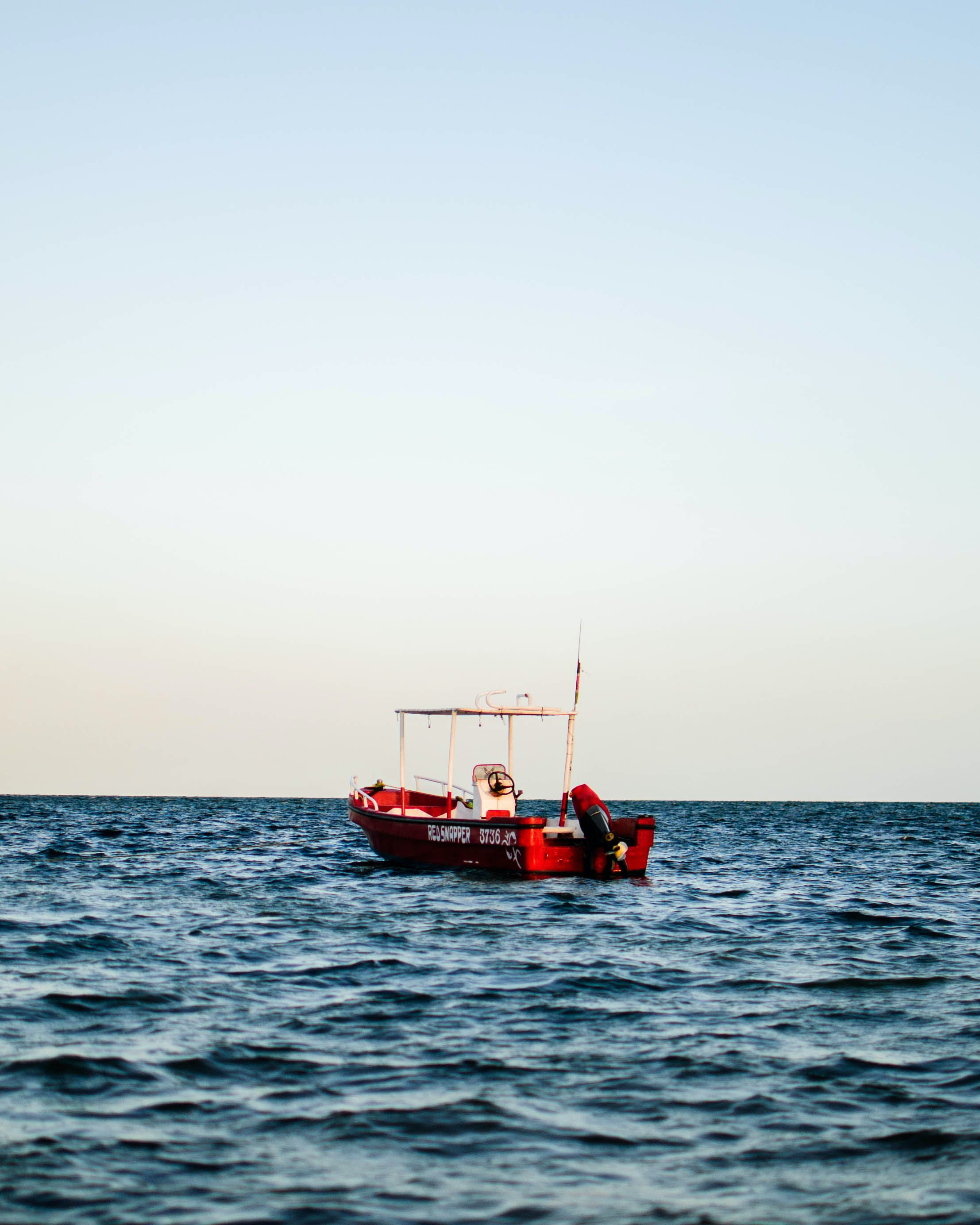 Red and White Boat on Body of Water
