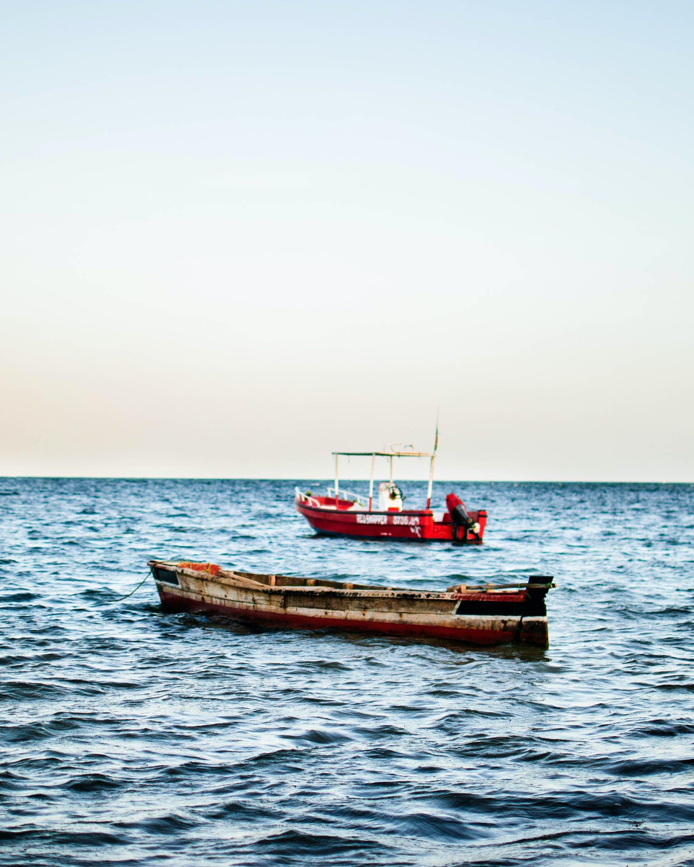 Brown Boat Beside Red Vessel
