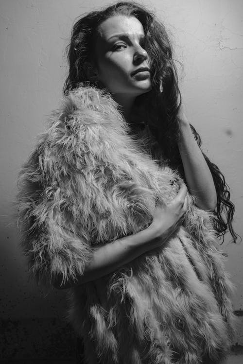 Grayscale Photography of Woman Standing Wearing Fur Coat