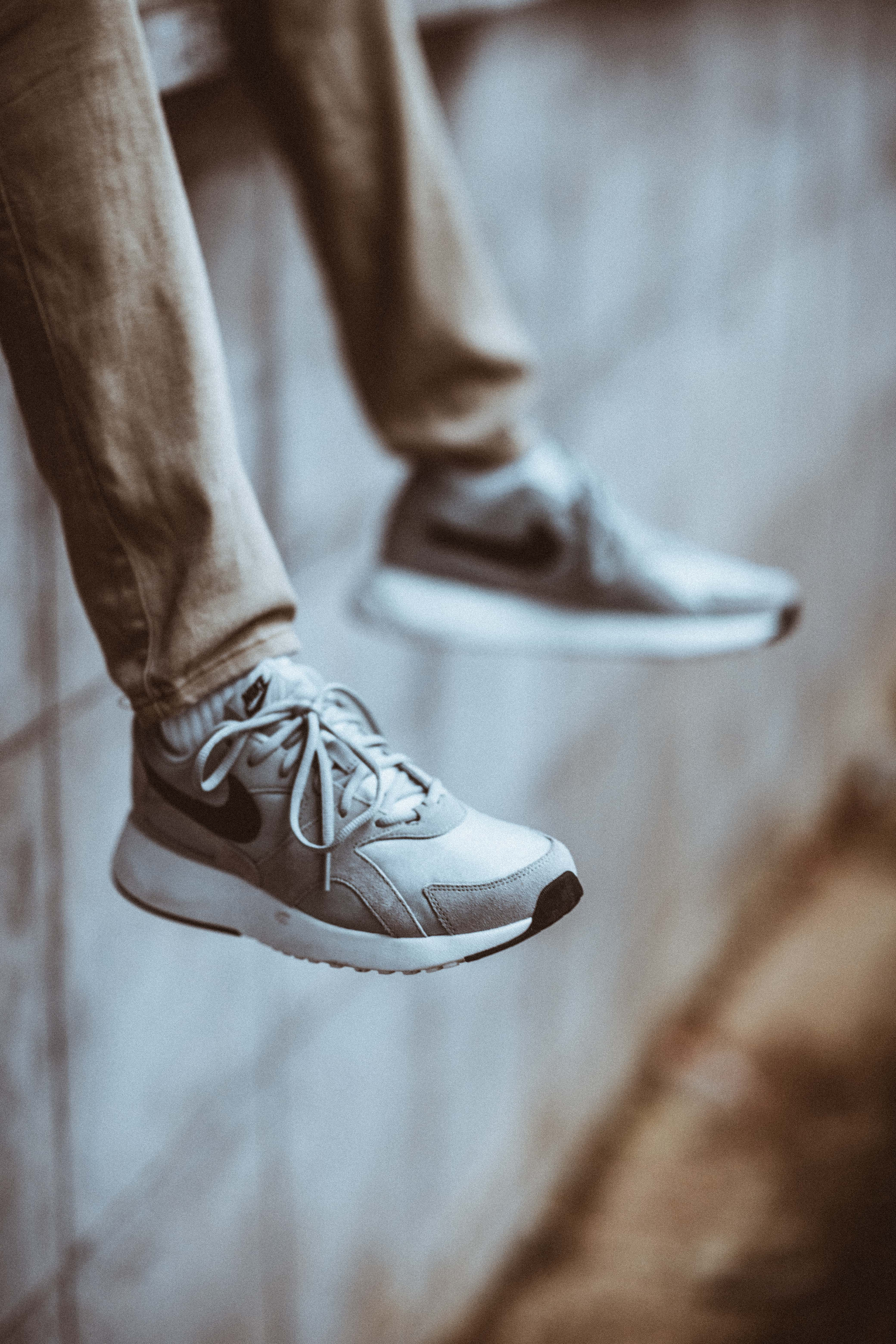 Selective Focus Photo of Person Wearing Gray Nike Shoes