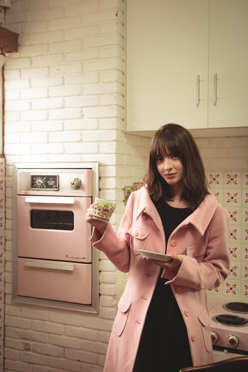 Woman Wearing Pink Coat Holds Cup and Saucer at the Kitchen Area