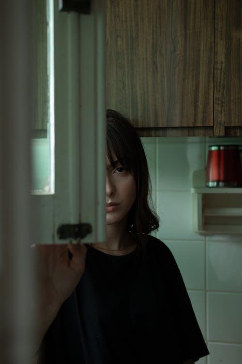 Женщина, стоящая в черной рубашке на кухне