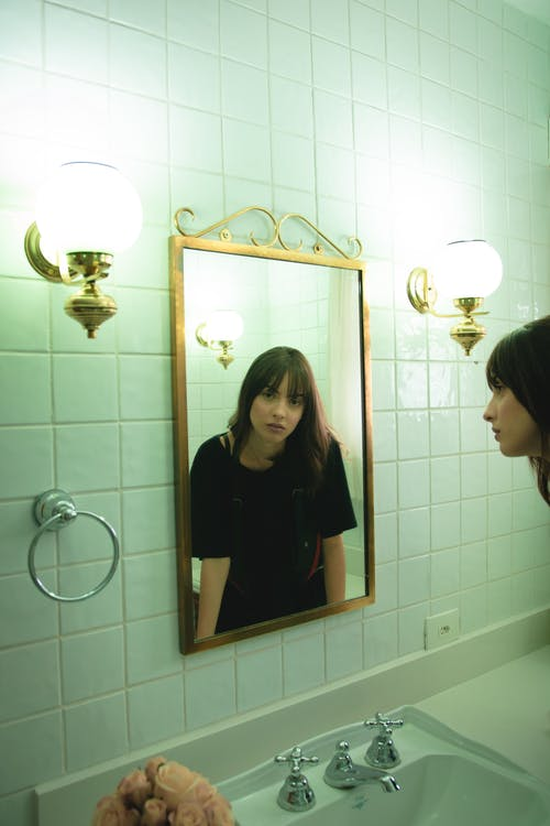 Woman in Black T-shirt Staring on Wall Mirror