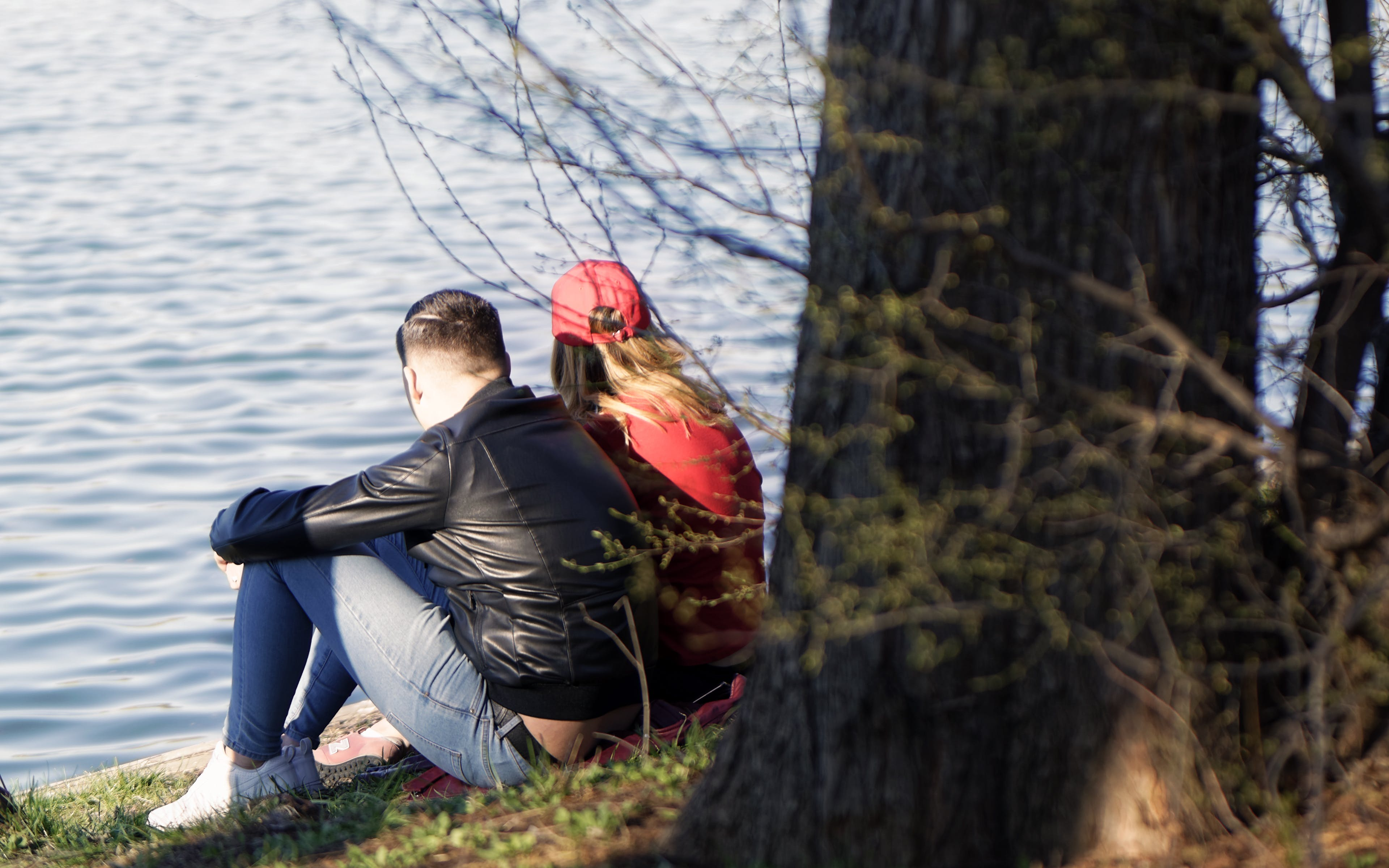 Free stock photo of nature, tree trunk, water, young couple relaxing near a body of water
