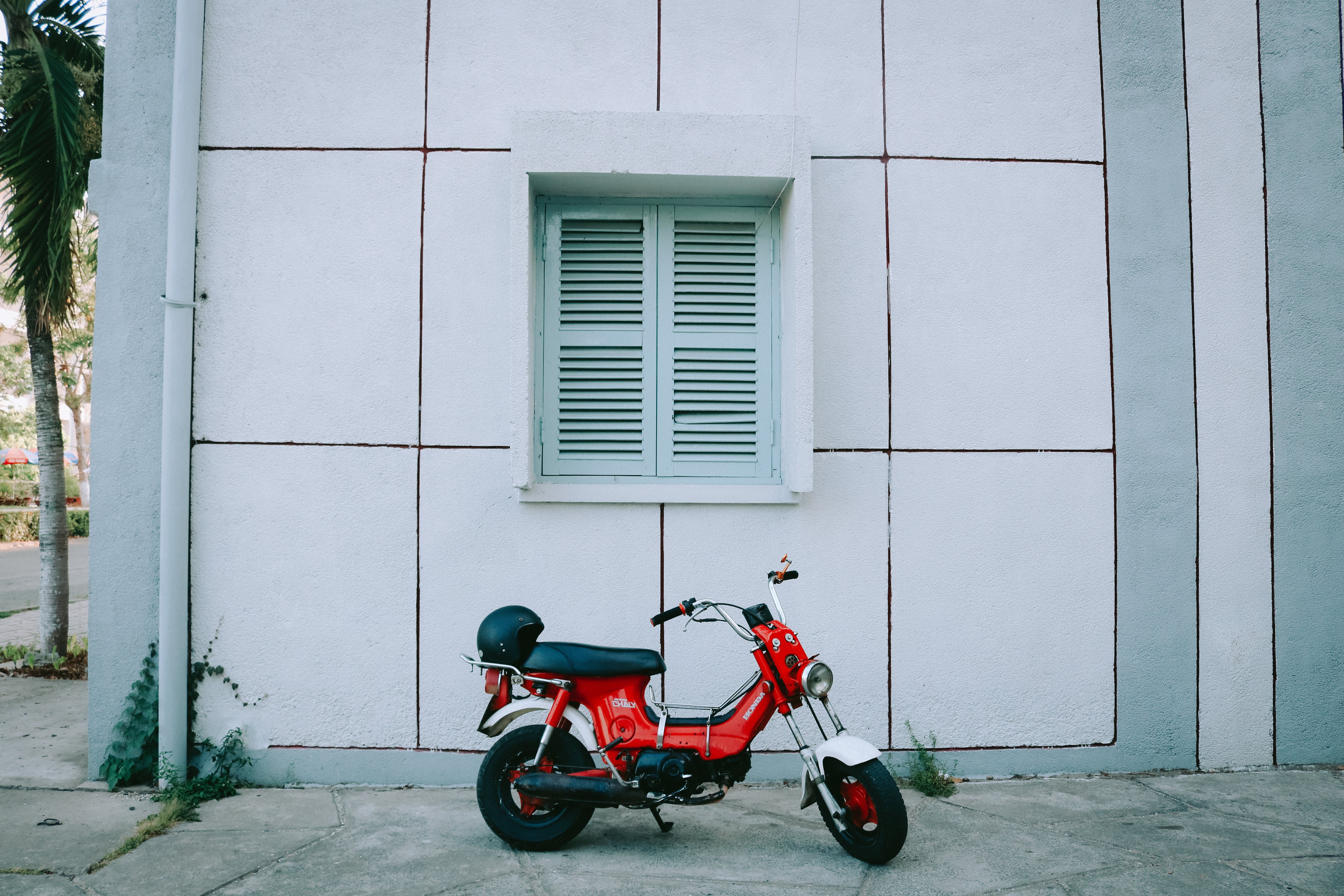 Red Motor Scooter Parked Beside White Concrete Building