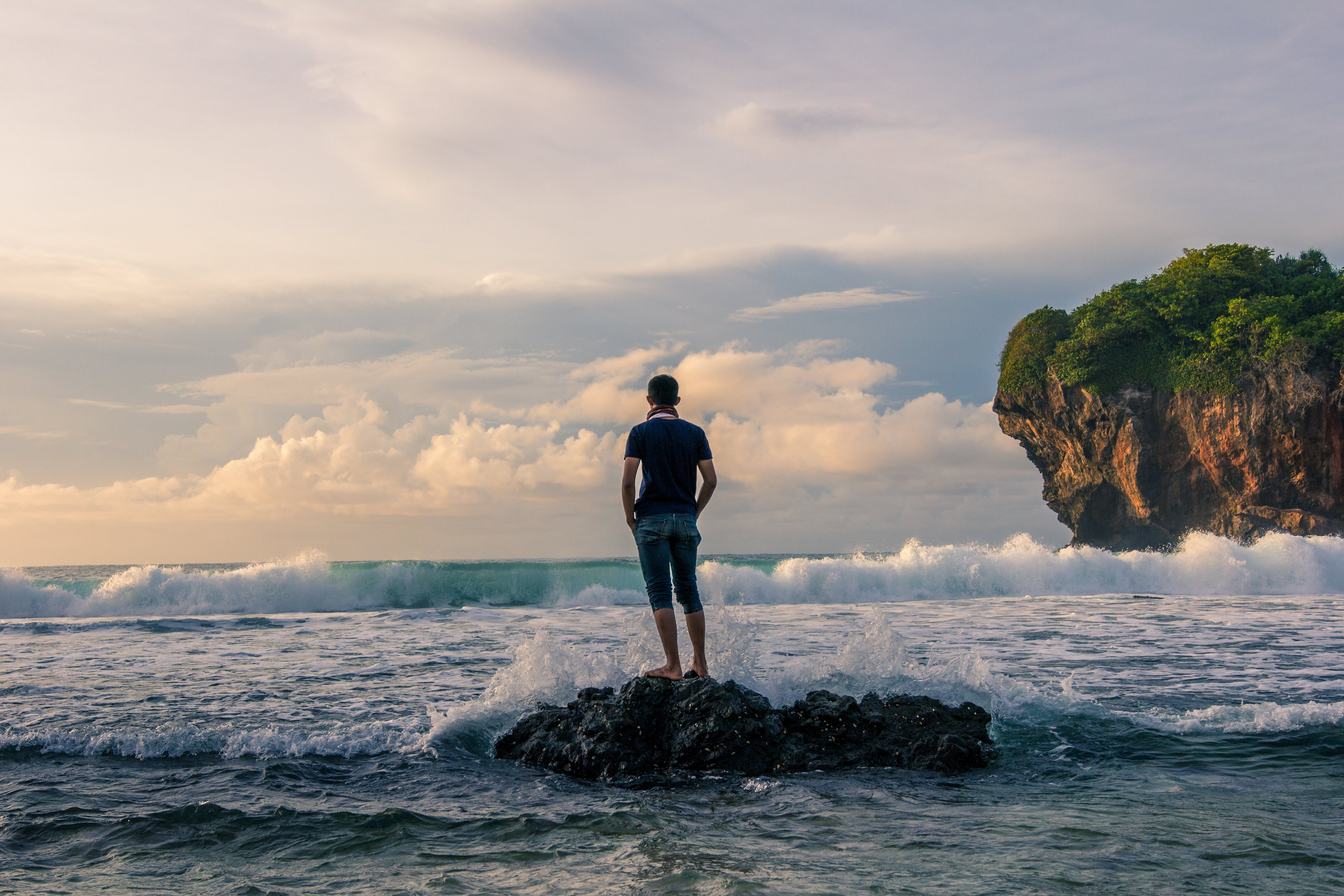 Man Standing on Stone Near Seashore during Sunrise Photography