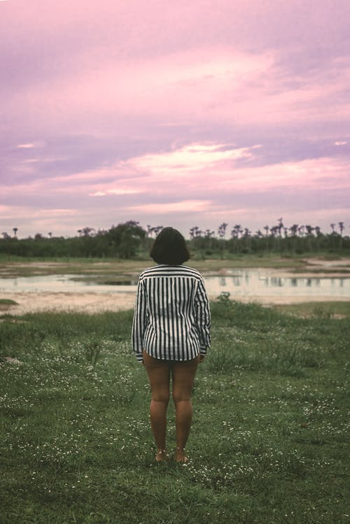 Back view of anonymous female traveler in casual clothes standing on grassy meadow near pond and admiring amazing sunset in countryside