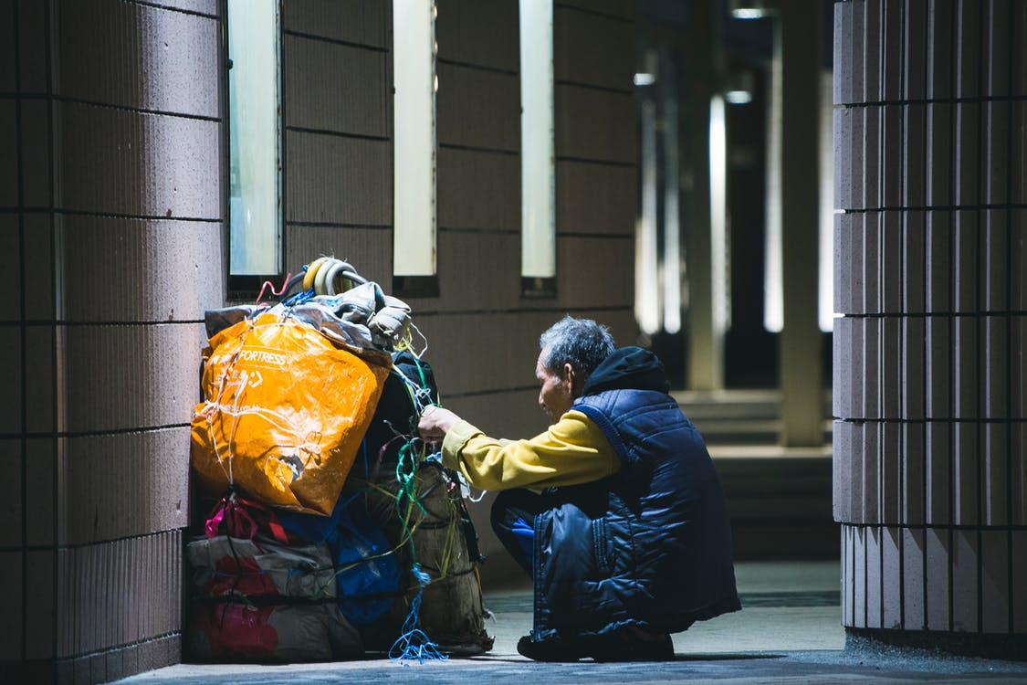 Man Sitting in Front of Bundled Bags