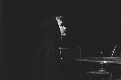 Person Standing in Front on Drum and Cymbals Grayscale Photography