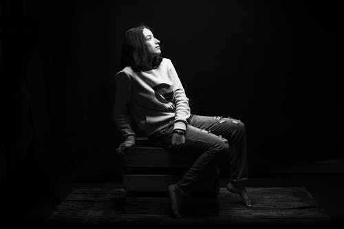 Grayscale Photo of Woman Sitting on Wooden Crate