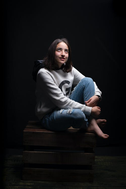 Photo of Woman Sitting on Brown Wooden Crate