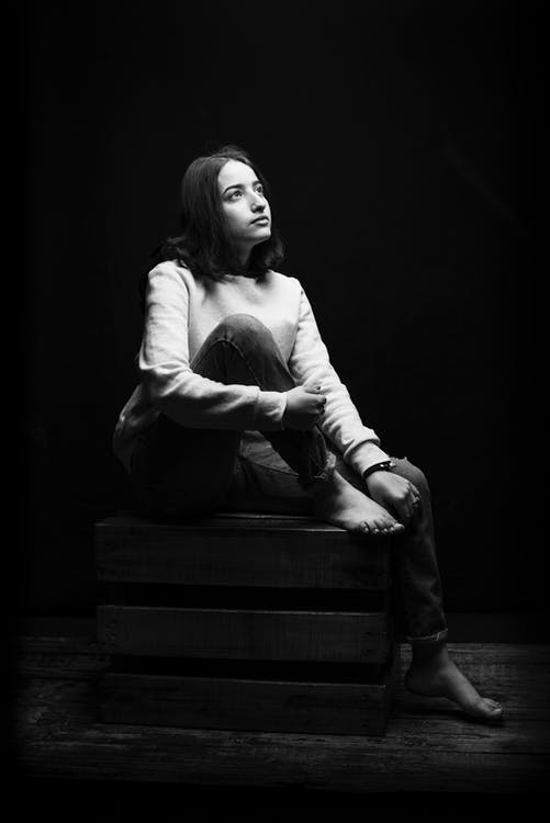 Grayscale Photo of Woman Sitting on a Wooden Crate While Looking Up