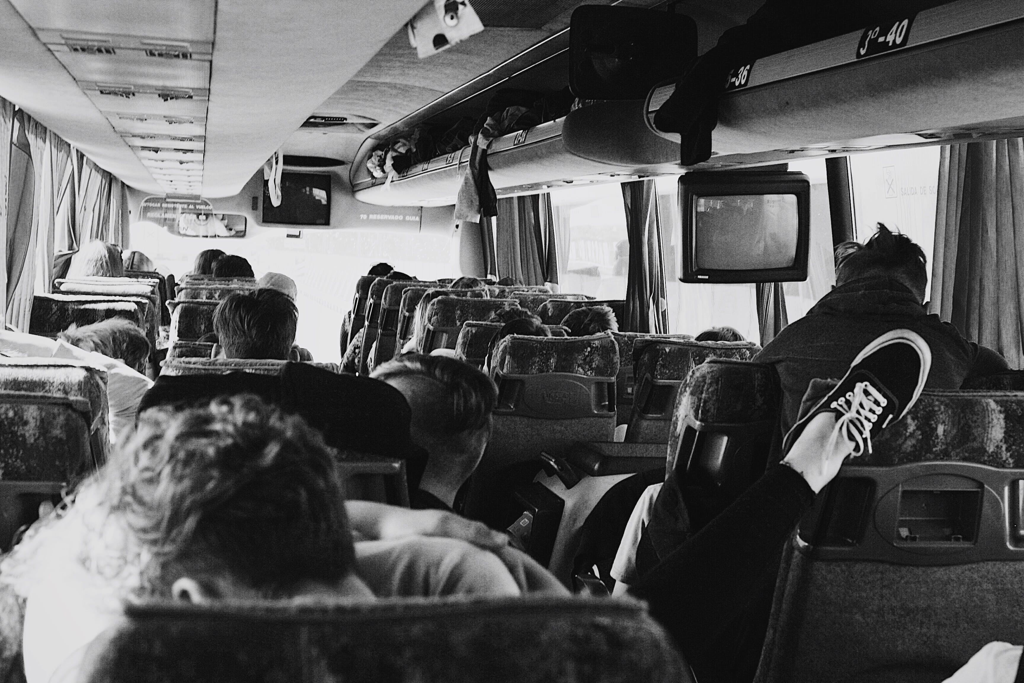 Grayscale Photo of People on a Bus