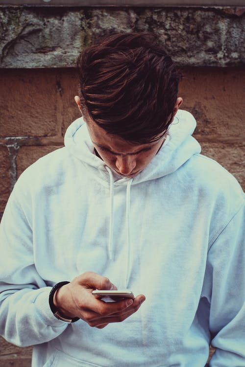 Photo of Man in White Hoodie Standing Near Brown Wall While Using His Smartphone