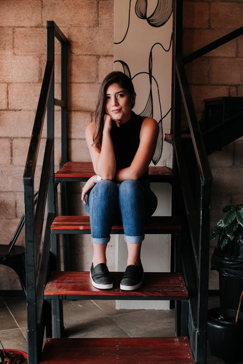 Woman in Blue Denim Jeans Sitting on Brown Stair