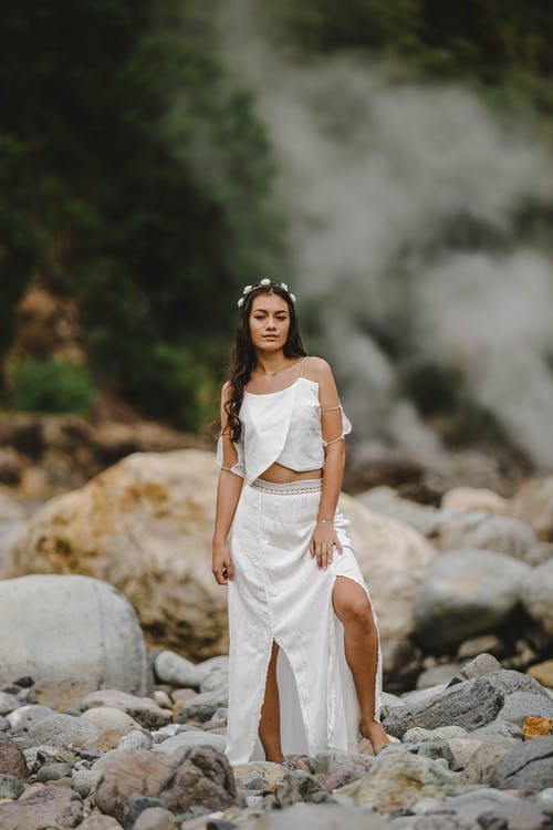 Photo of Woman in White Outfit  and Flower Crown Standing on Rocks