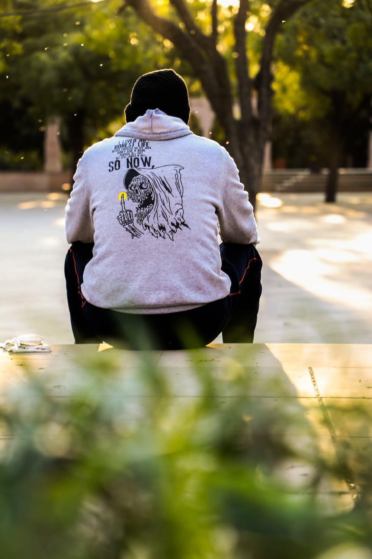 Man sitting on a pavement. | Photo: Pexels