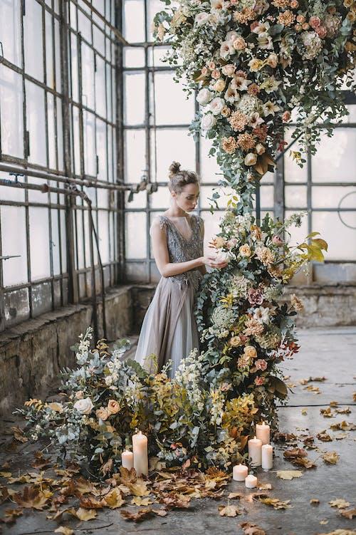 Woman Standing Beside Flowers Inside Building