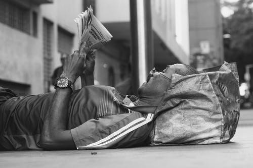 Monochrome Photo of Man Reading Newspaper