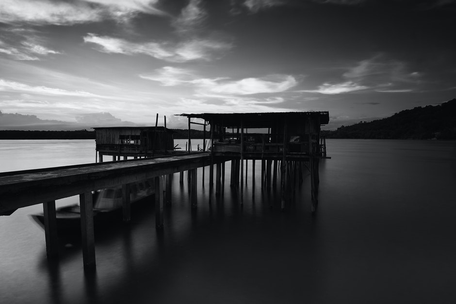 Greyscale Photo of Dock Near Mountains