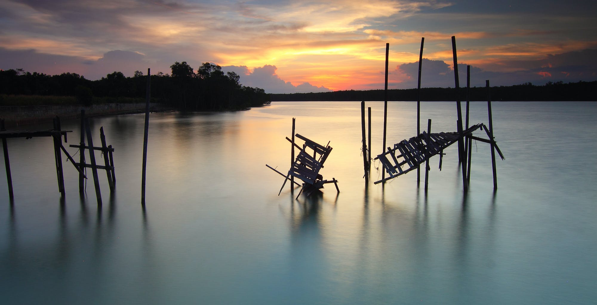 Silhouette of Broken Boardwalk on Body of Water Under Sunset