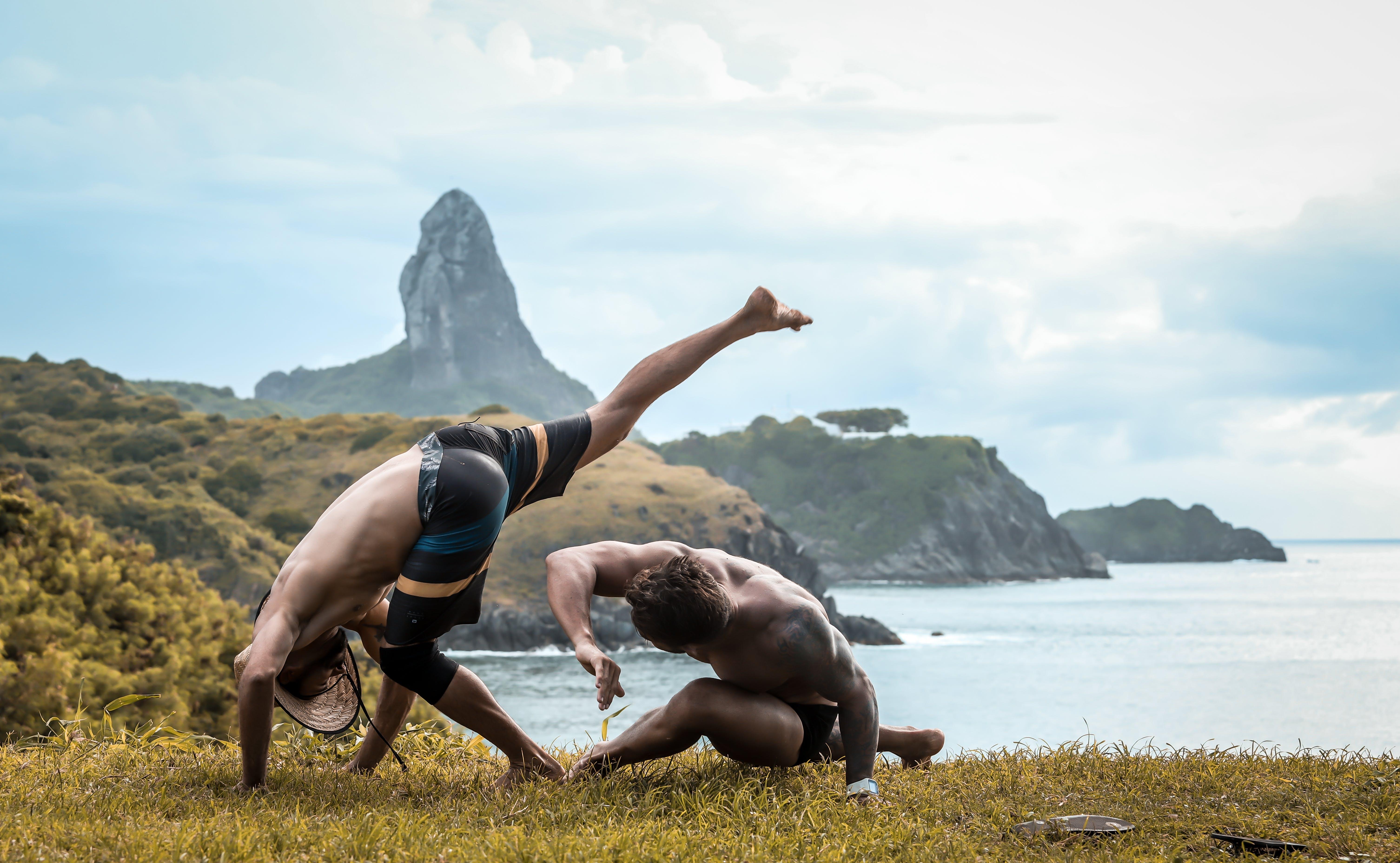 2 Men Performing Capoeira on Grass