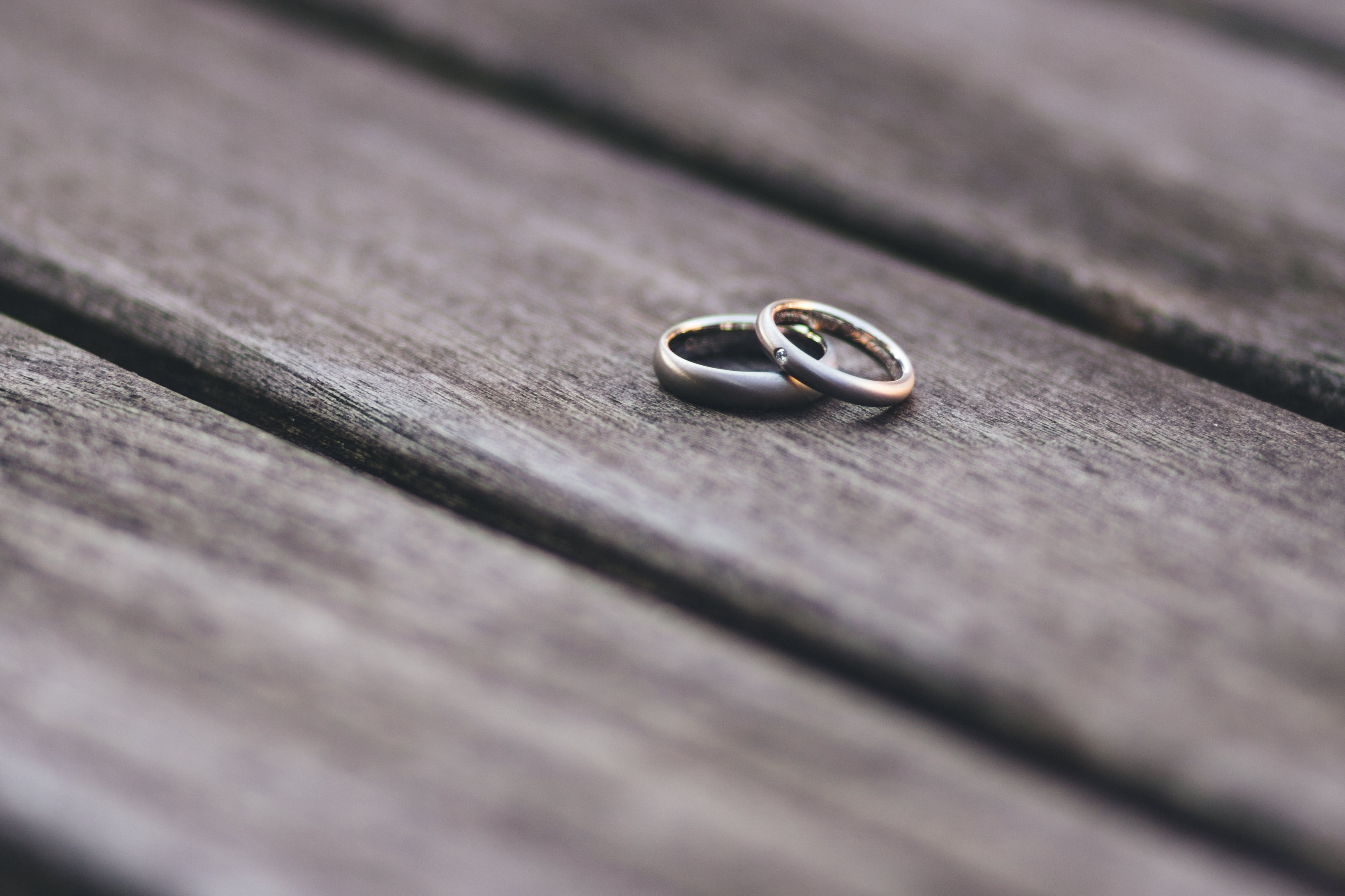 couple rings on top of a wooden bench