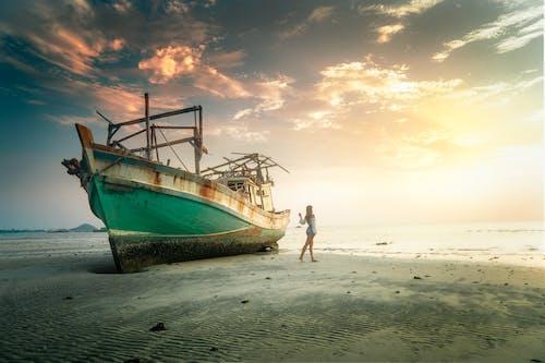 Foto profissional grátis de alvorecer, areia, barco, beira-mar
