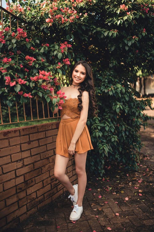 Woman Wearing Brown Sleeveless Pleated Mini Dress