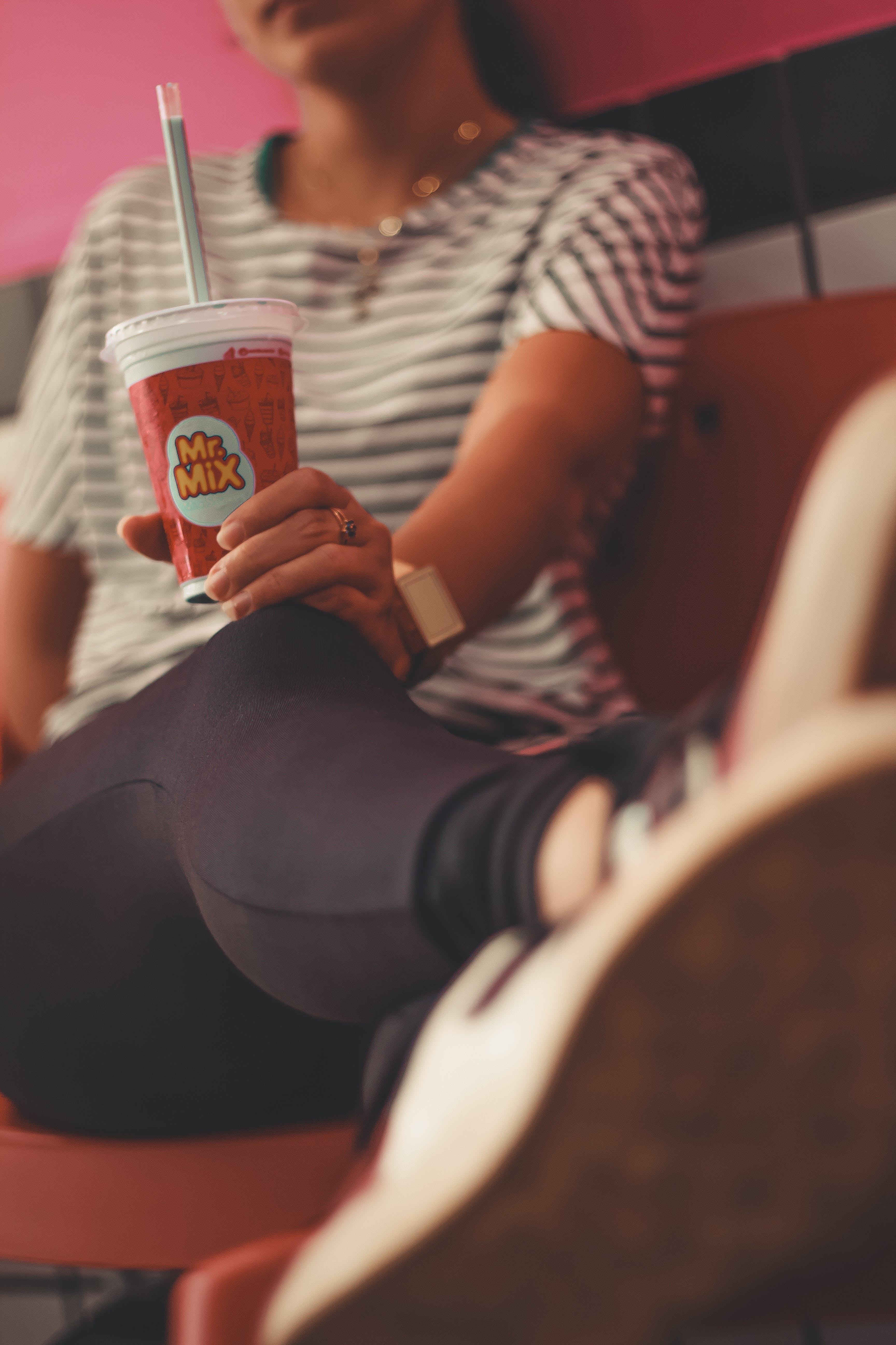 Photo of Woman Holding Mr. Mix Plastic Milkshake Cup While Sitting
