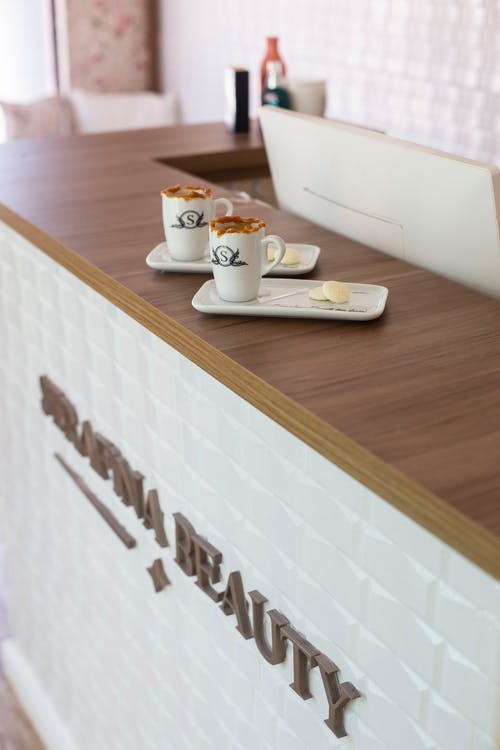 Shallow Focus Photo of White Ceramic Mugs on Brown Wooden Counter Table