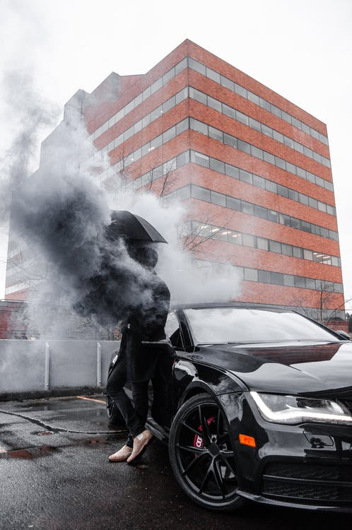 Photo of Man Leaning On Black Car