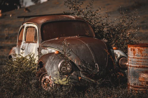 Photo of Abandoned Vintage Volkswagen Beetle Near Rusty Drum