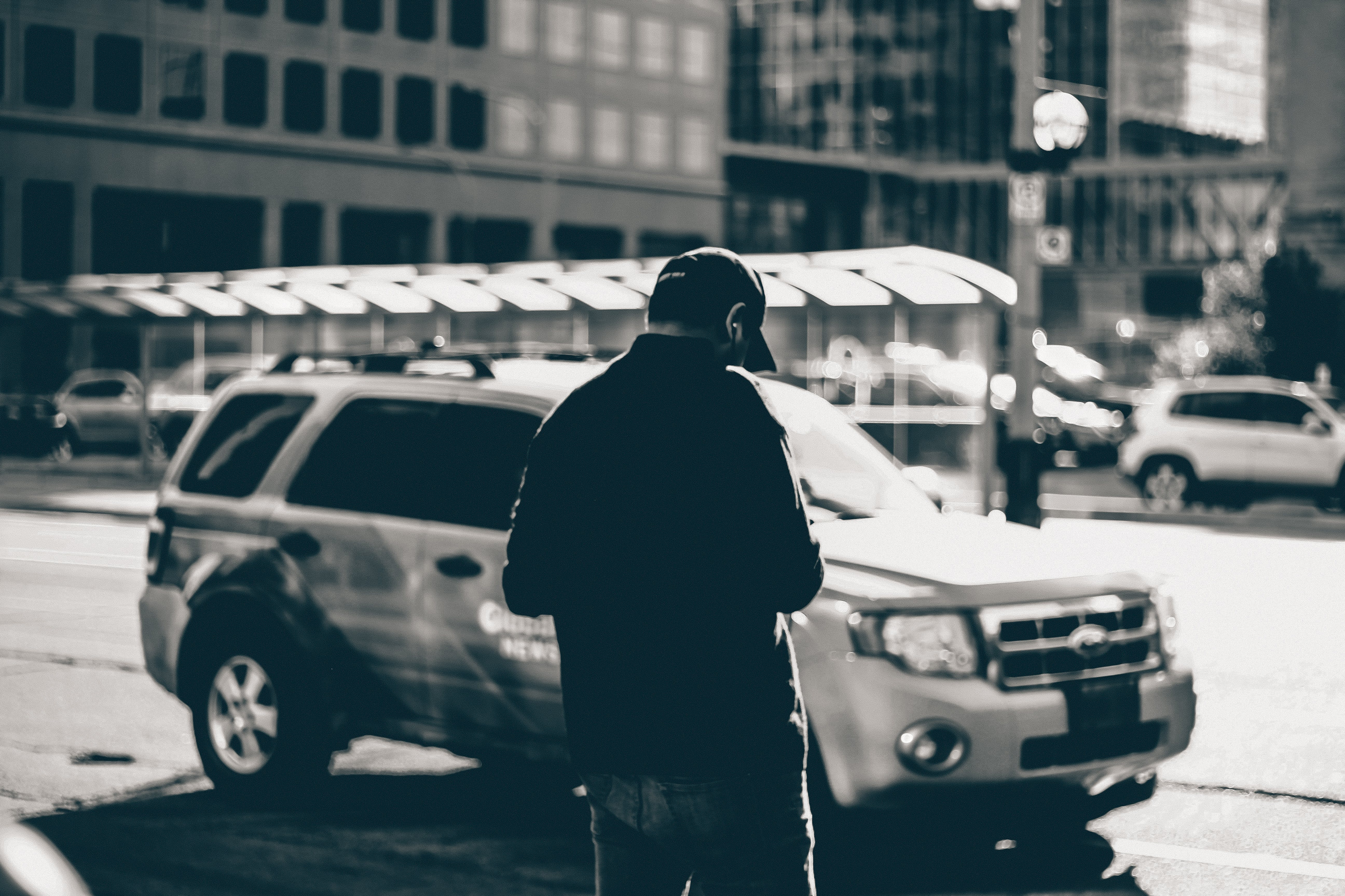 Grayscale Photography of Man Standing Near Suv during Daytime