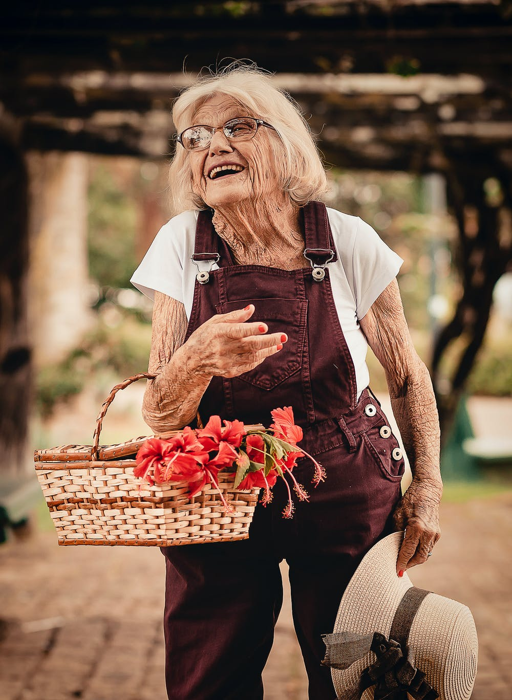 Old woman holding sunhat and picnic basket | Photo: Pexels