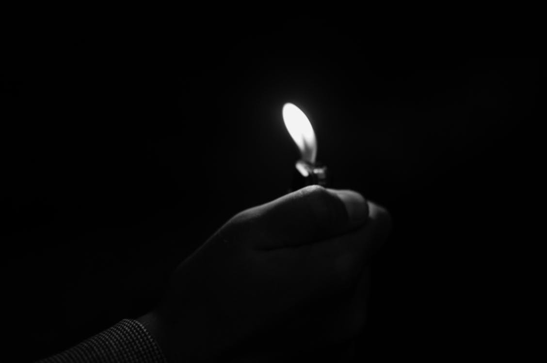 Close-up of Hand Holding Candle in Darkroom