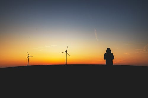 Silhouttte Photography of Person Standing Near Turbines