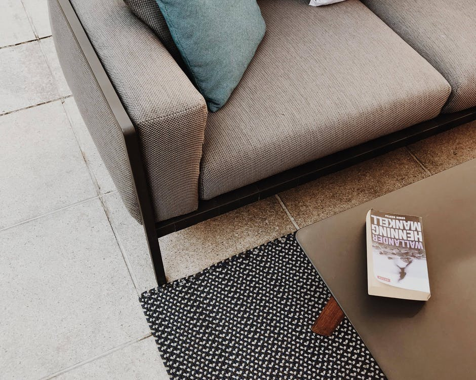 White and Brown Book on Table Near Couch
