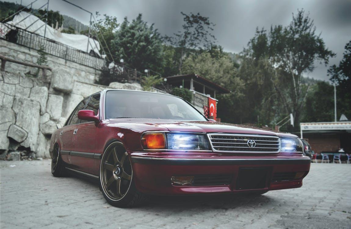 Red Toyota Sedan With Headlights on