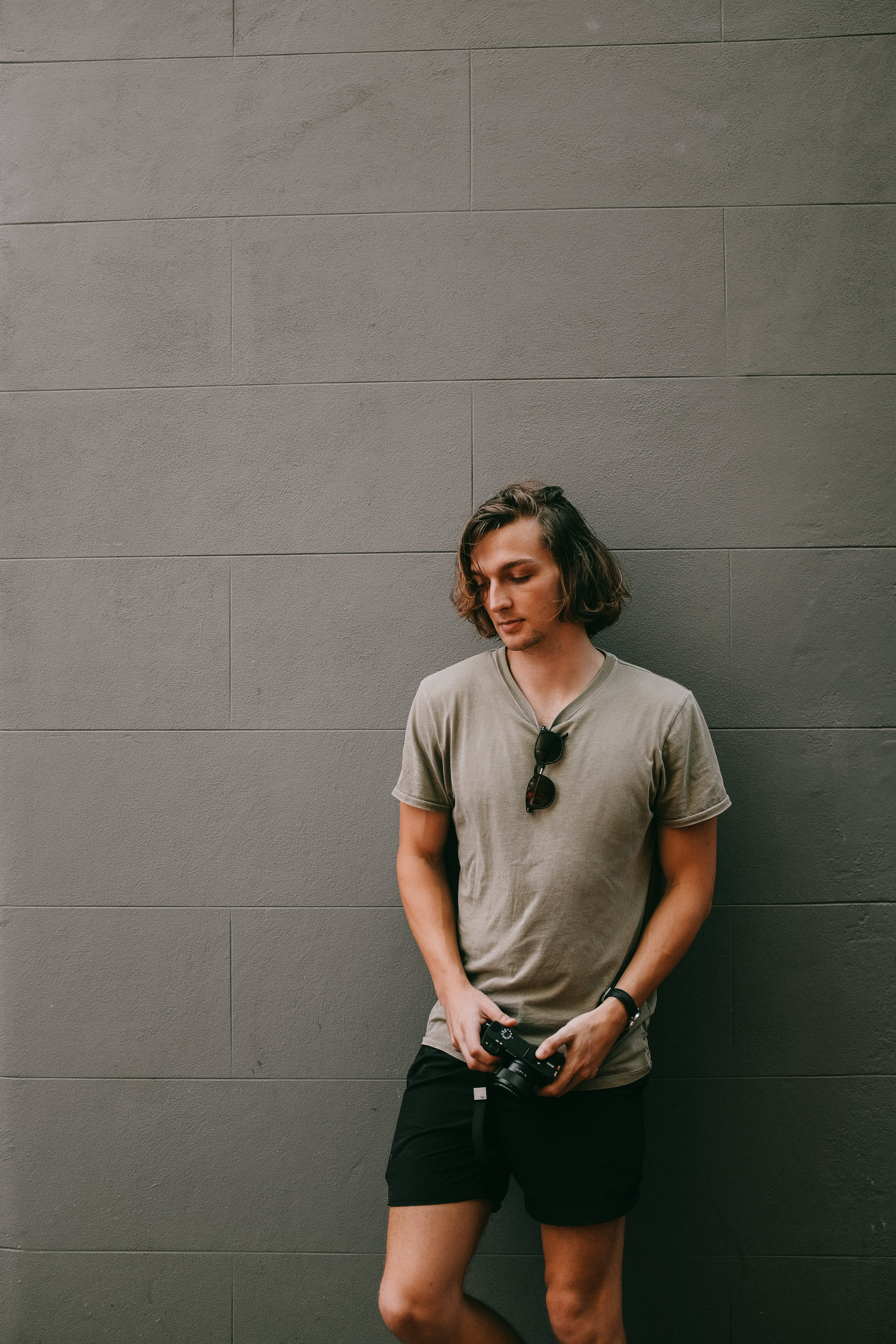 Man in Gray Tee Shirt Holding Camera While Leaning on Wall