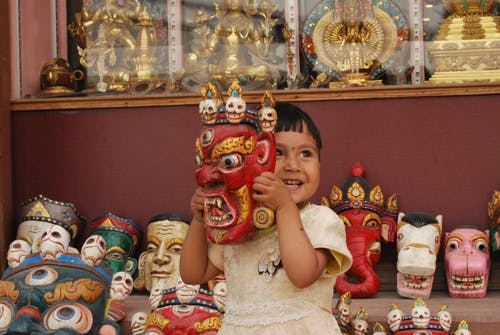 Toddler Smiling and Holding Red Mask