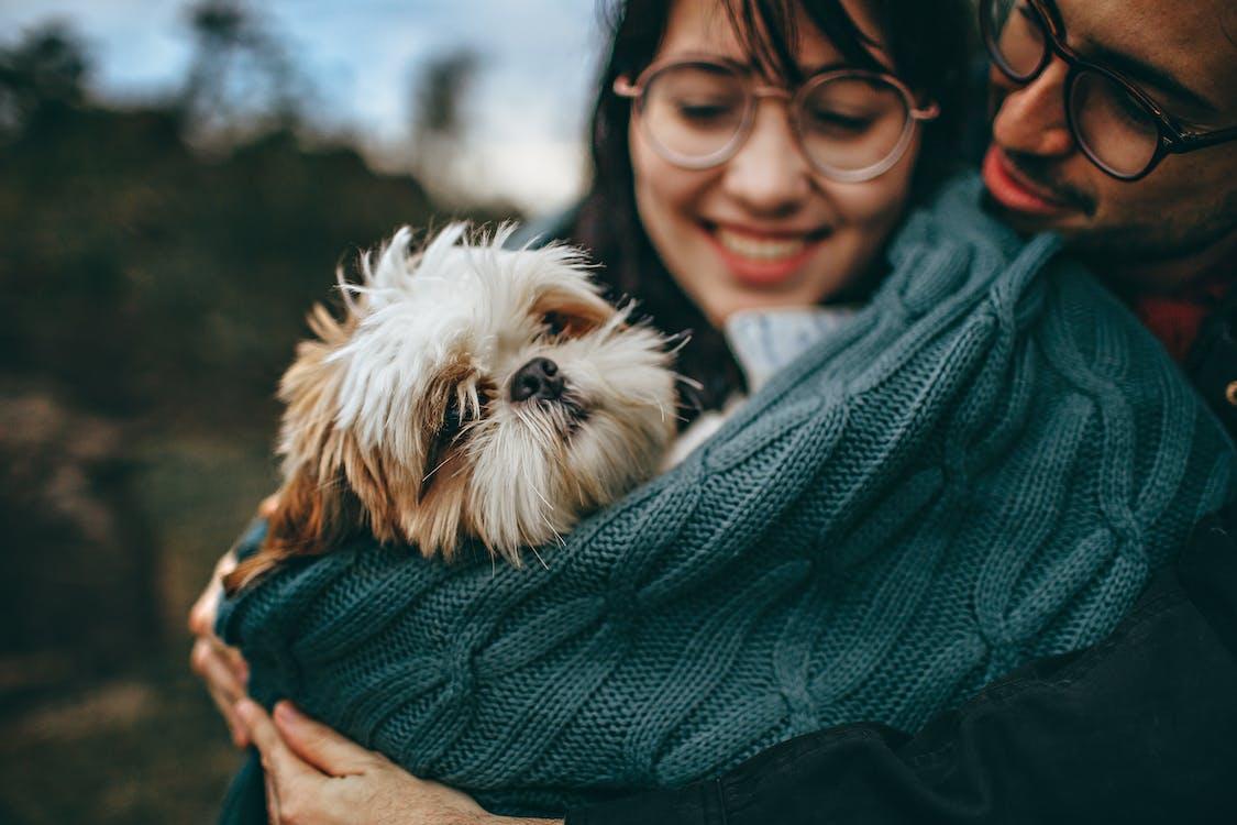 Woman and Man Hugging Dog
