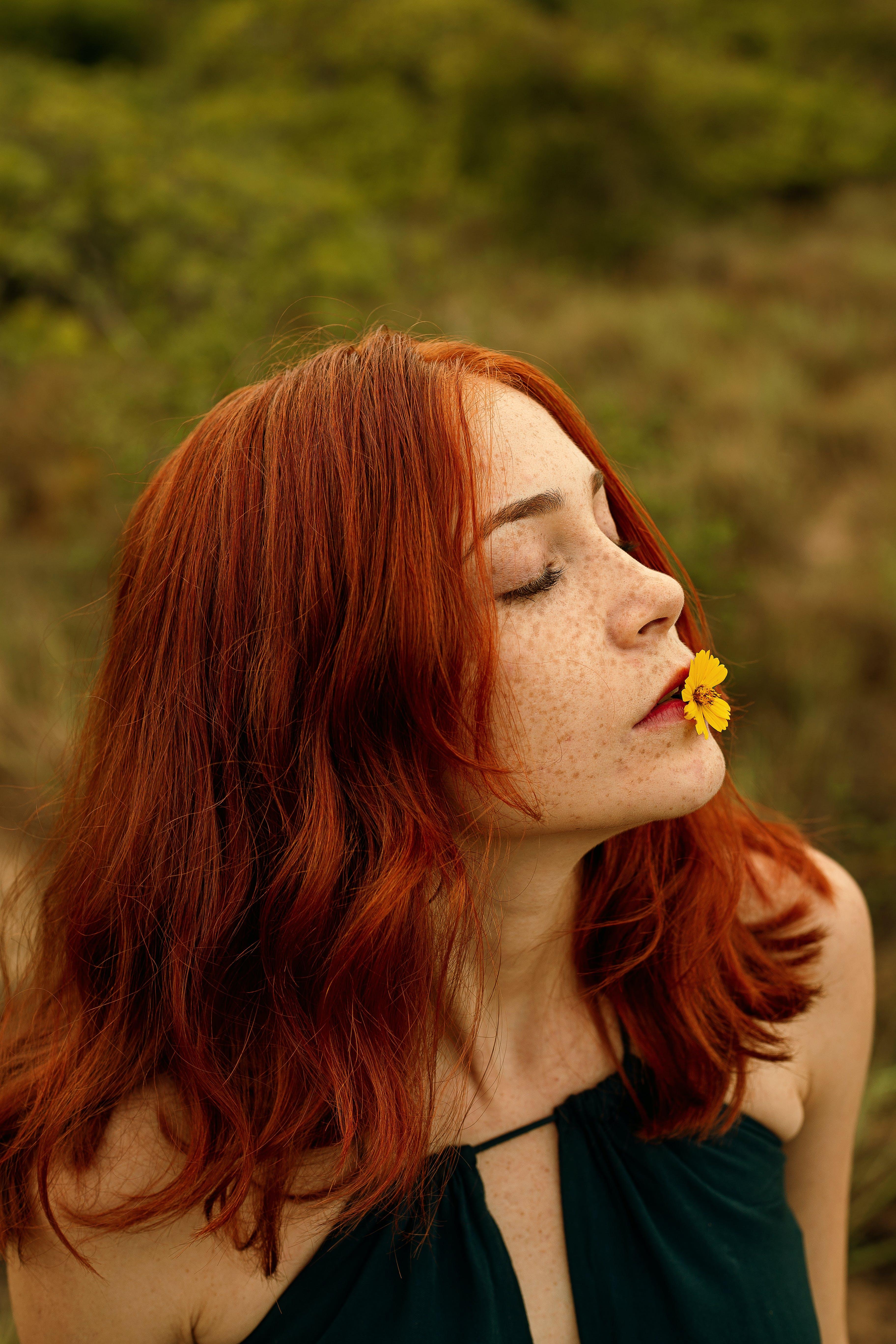 Foto d'estoc gratuïta de cabells pèl-roigs, dona, flor groga, foto vertical