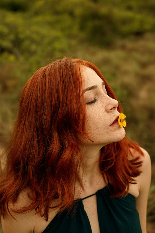 Photo of Red-haired Woman With Yellow Petaled Flower on Her Lips