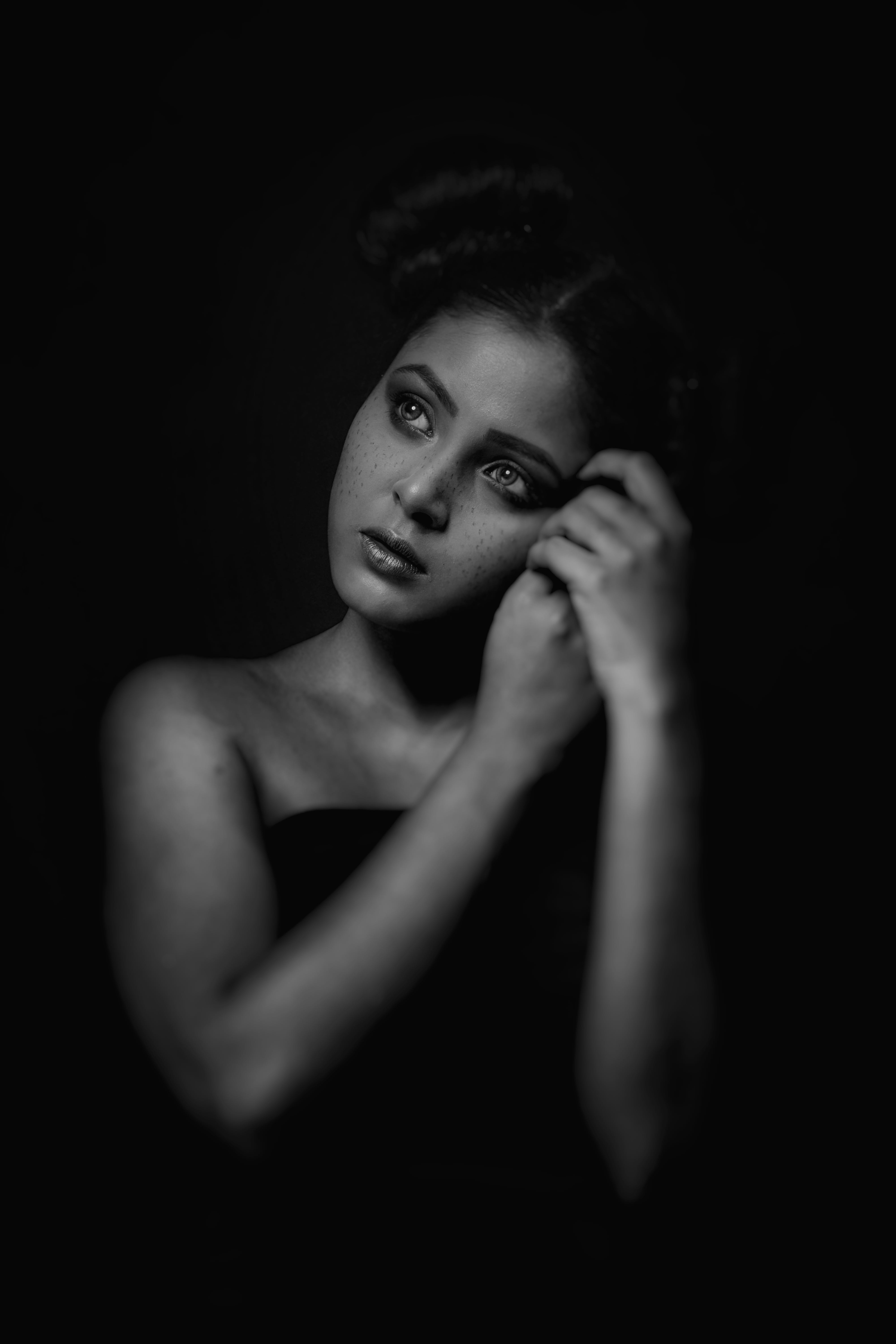 Grayscale Photo of Woman in Dark Room Posing